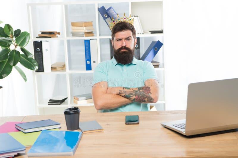 Impiegato del mese Il capo indifferente dell'uomo con la corona dorata si siede in ufficio Superiorità ed auto fiducia Capo di re immagini stock libere da diritti