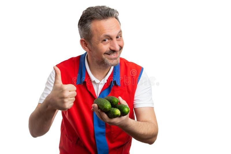 Impiegato del supermercato che fa pollice sul gesto con i cetrioli a disposizione immagine stock