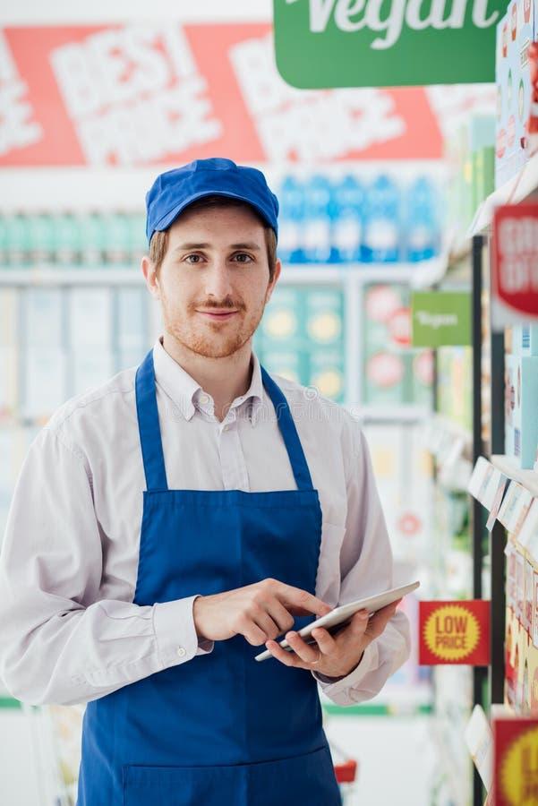 Impiegato del supermercato facendo uso di una compressa immagini stock libere da diritti