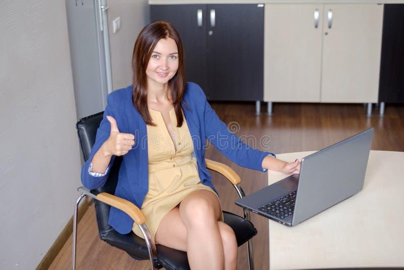 Impiegato di concetto allegro che mostra i pollici su davanti al computer portatile fotografia stock libera da diritti