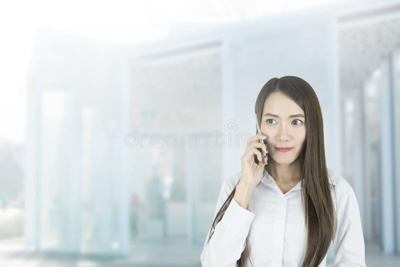 Impiegato di concetto asiatico della donna di affari che comunica con il telefono cellulare fotografie stock libere da diritti