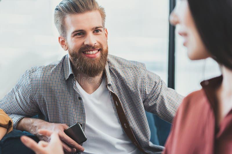 Impiegato di concetto barbuto sorridente felice che tiene telefono immagine stock
