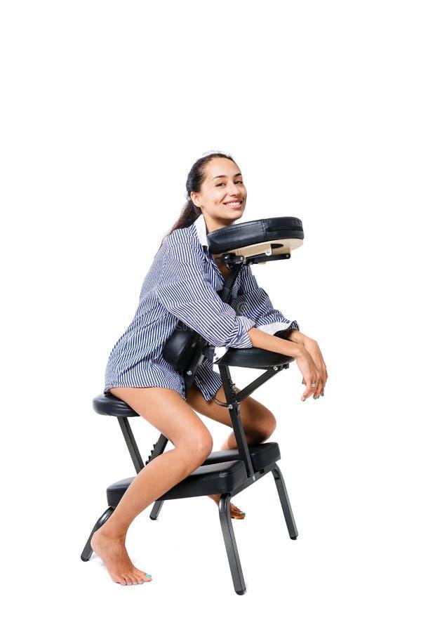 Impiegato di concetto castana della giovane bella ragazza in una camicia e con le gambe nude che si siedono su una sedia di massa fotografia stock libera da diritti