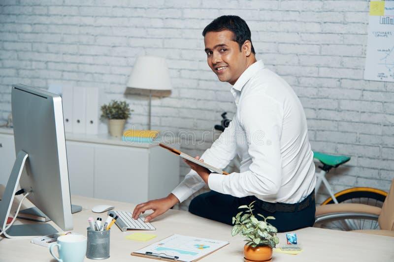 Impiegato di concetto che utilizza il pc della compressa e del computer nel suo lavoro immagini stock libere da diritti