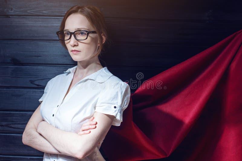Impiegato di concetto della superdonna che sta in un vestito ed in un mantello rosso fotografie stock libere da diritti