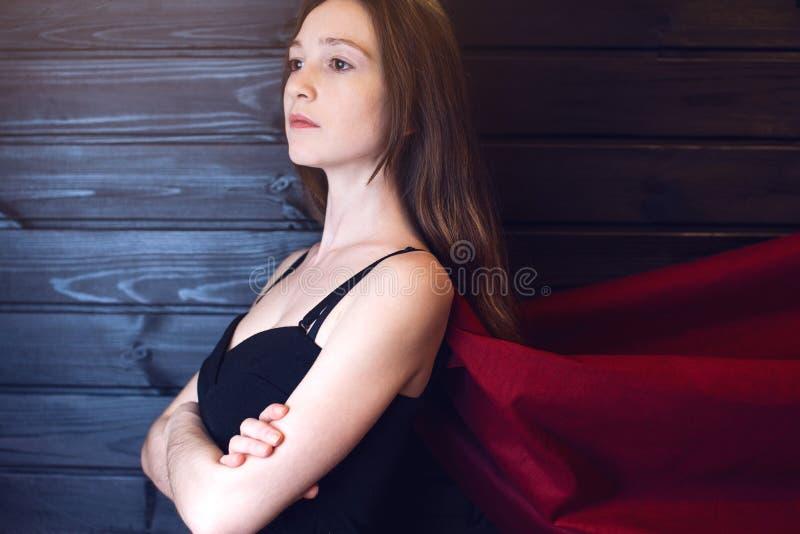 Impiegato di concetto della superdonna che sta in un vestito ed in un mantello rosso fotografia stock