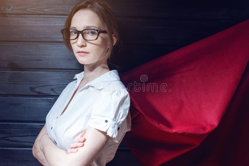 Impiegato di concetto della superdonna che sta in un vestito ed in un mantello rosso fotografie stock