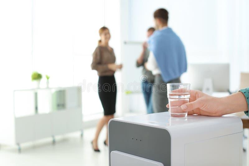 Impiegato di ufficio con vetro vicino al dispositivo di raffreddamento di acqua nel luogo di lavoro, primo piano immagine stock libera da diritti