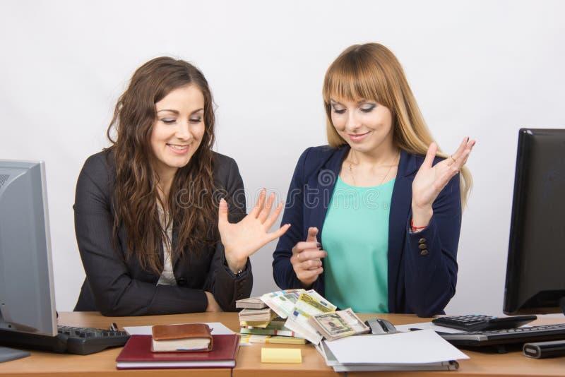 Impiegato di ufficio due che esamina molti soldi sulla tavola immagini stock