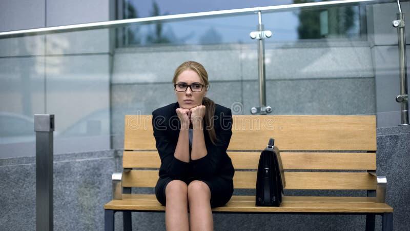 Impiegato di ufficio frustrato che si siede sul banco, stanco dopo la riunione stressante fotografia stock