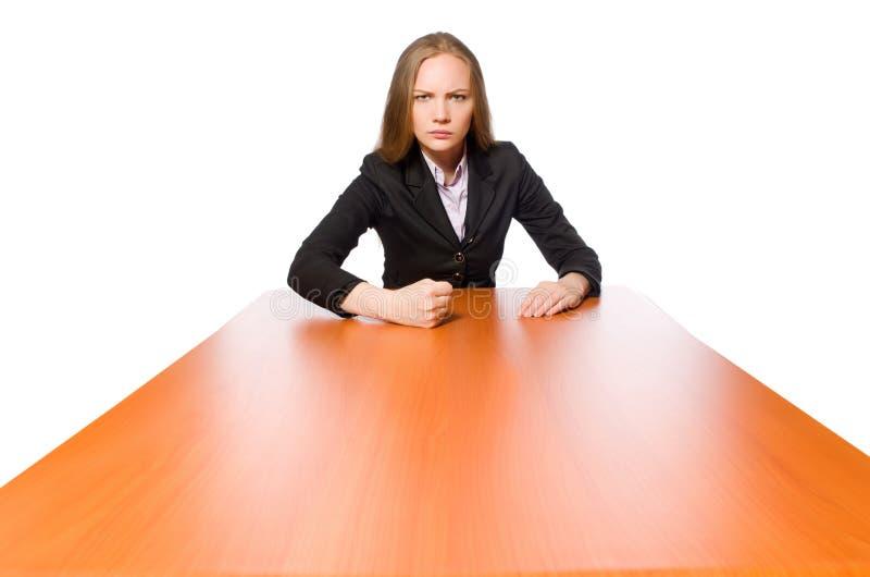 Impiegato femminile che si siede alla tavola lunga isolata sul bianco immagini stock