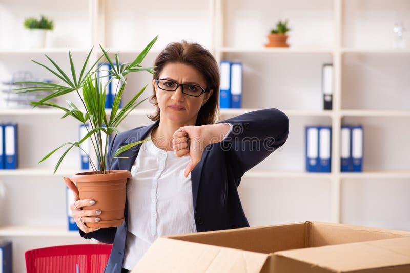 Impiegato femminile di mezza et? che ? infornato dal suo lavoro immagini stock