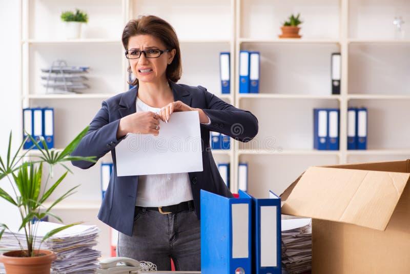 Impiegato femminile di mezza et? che ? infornato dal suo lavoro immagini stock libere da diritti