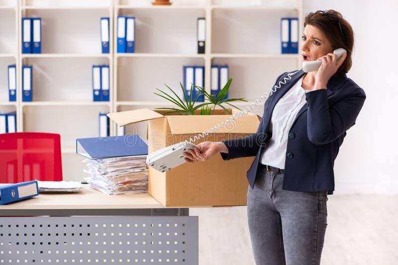 Impiegato femminile di mezza et? che ? infornato dal suo lavoro fotografia stock