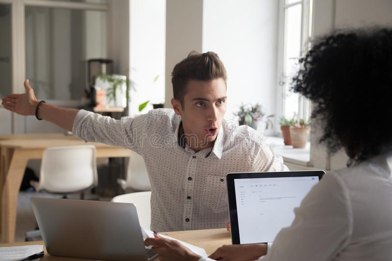 Impiegato maschio pazzo che incolpa del collega femminile l'errore immagine stock libera da diritti