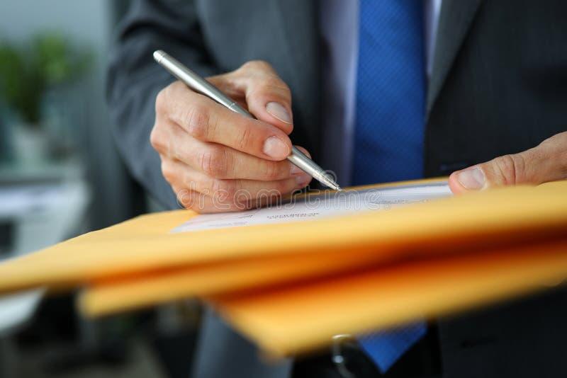 Impiegato maschio in vestito e legame alla tenuta del posto di lavoro nella penna d'argento delle mani che compila il modulo di d immagine stock