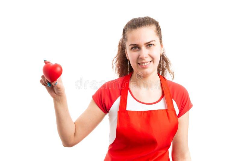 Impiegato o magazziniere del supermercato della donna che tiene il cuore rosso del giocattolo immagini stock