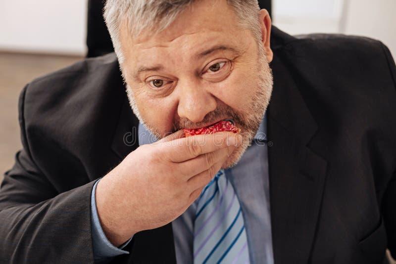 Impiegato obeso divertente che prende un morso di una ciambella immagini stock libere da diritti