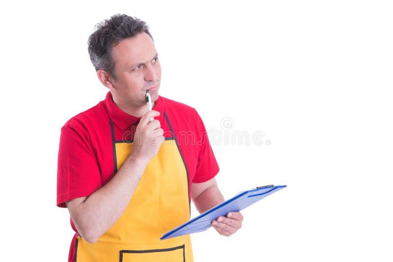 Impiegato pensieroso con la lavagna per appunti che sembra dubbiosa fotografia stock libera da diritti