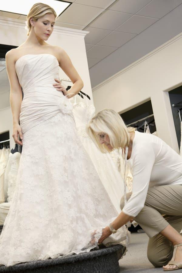 Impiegato senior che regola vestito da sposa di bella giovane sposa in deposito nuziale immagini stock libere da diritti