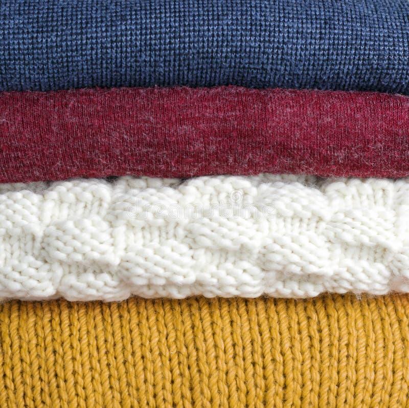 Impilato dei maglioni tricottati di lana multicolori primo piano, struttura, fondo immagini stock