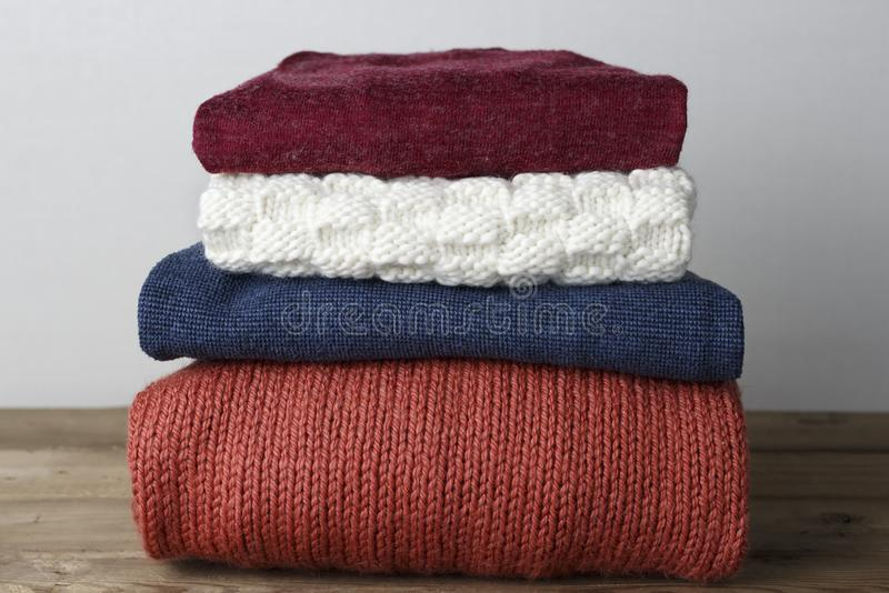 Impilato del primo piano tricottato di lana multicolore dei maglioni, su fondo di legno, vista frontale fotografia stock