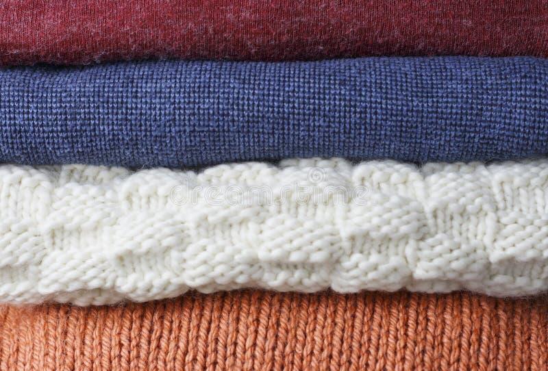 Impilato del primo piano tricottato di lana multicolore dei maglioni, su fondo di legno, vista frontale fotografia stock libera da diritti