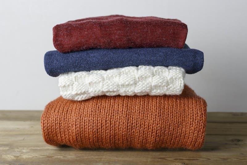 Impilato del primo piano tricottato di lana multicolore dei maglioni, su fondo di legno, vista frontale fotografie stock