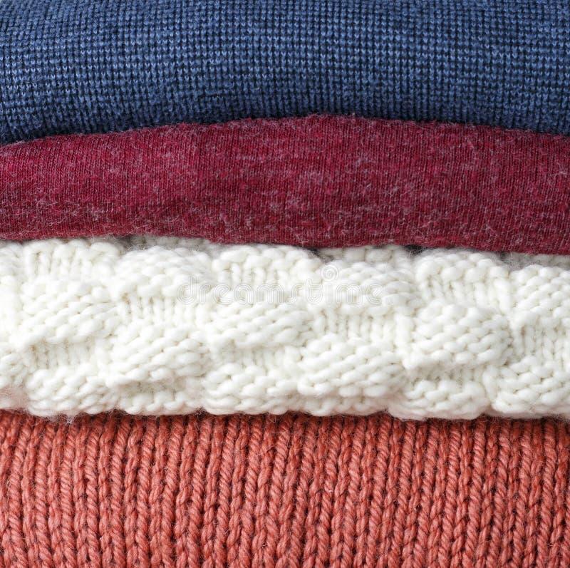 Impilato del primo piano tricottato di lana multicolore dei maglioni, su fondo di legno, vista frontale immagini stock