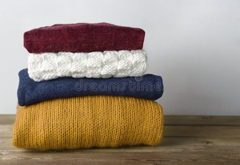 Impilato del primo piano tricottato di lana multicolore dei maglioni, su fondo di legno, vista frontale fotografie stock libere da diritti