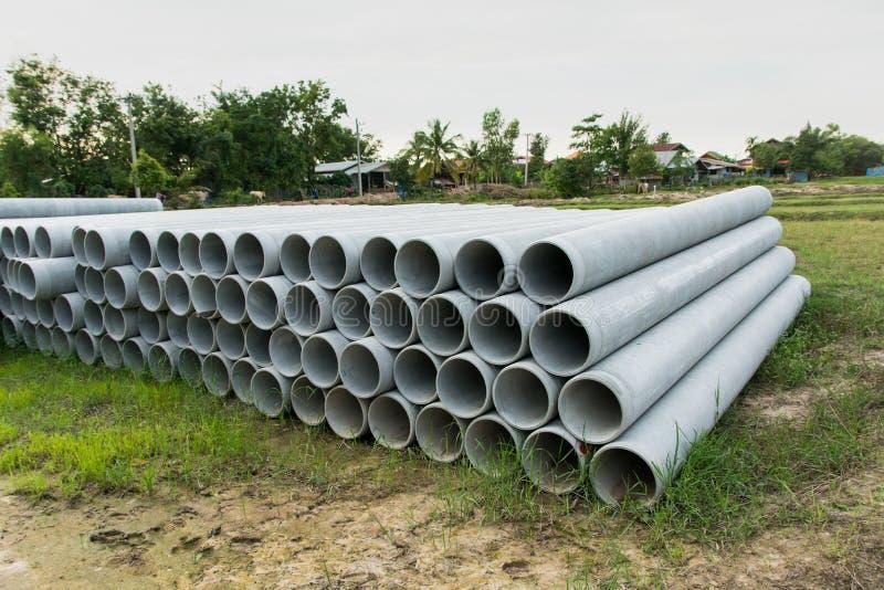 Impilato di concreto, tubi del cemento tubi concreti per irrigazione al cantiere fotografia stock