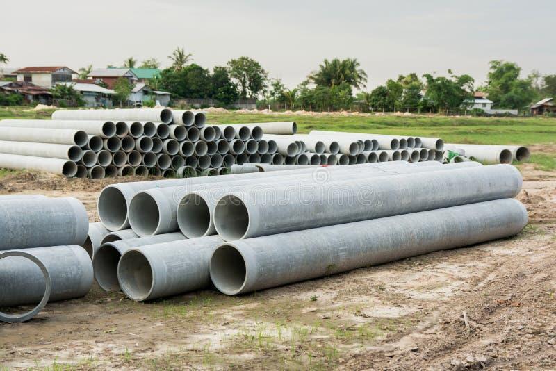 Impilato di concreto, tubi del cemento tubi concreti per irrigazione al cantiere immagine stock libera da diritti