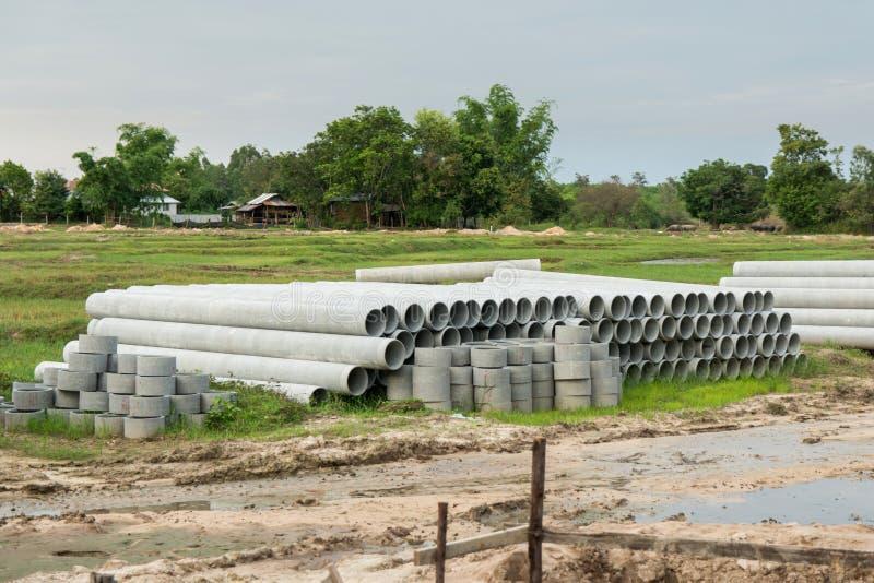 Impilato di concreto, tubi del cemento tubi concreti per irrigazione al cantiere fotografia stock libera da diritti