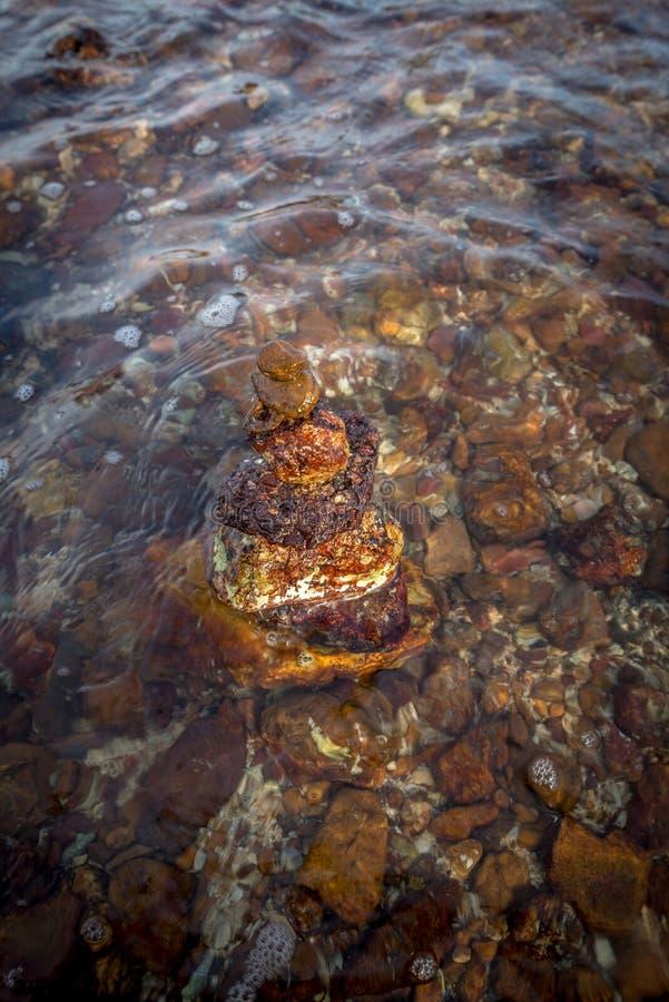 Impilato di roccia nel mare d'ondeggiamento immagine stock
