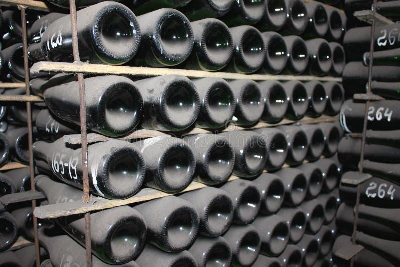 Impilato sulle bottiglie di vino nella cantina fotografia stock