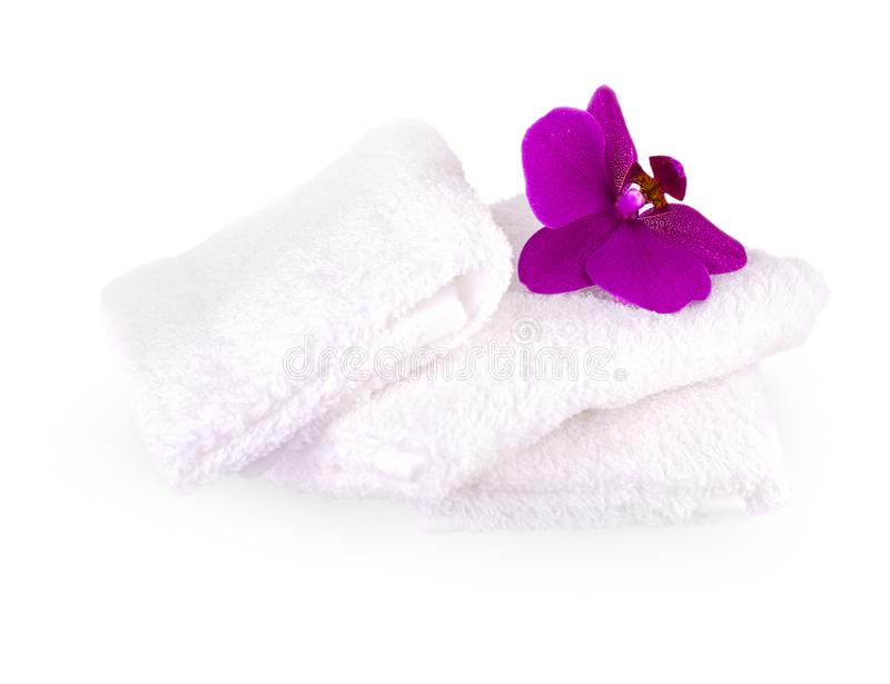 Impili gli asciugamani bianchi della stazione termale su fondo bianco con l'orchidea porpora immagini stock