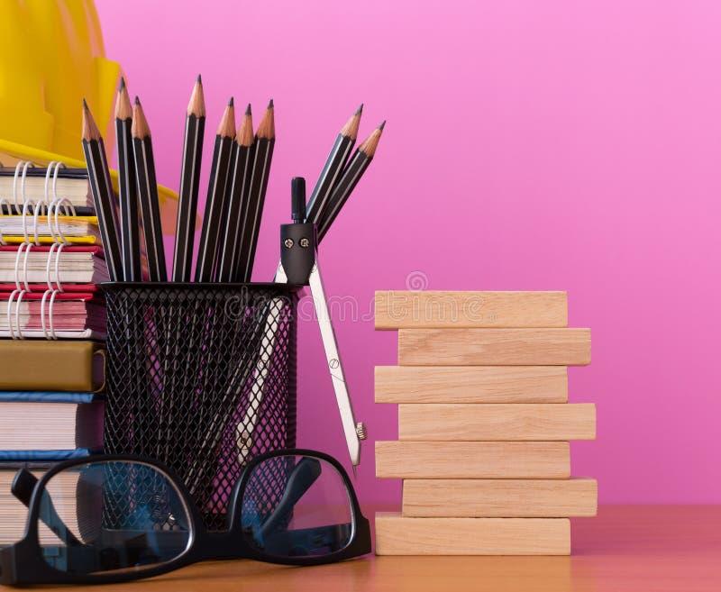 Impili i blocchi di legno con le matite, i divisori, i vetri, il casco della costruzione e la pila di libro sulla tavola di legno immagini stock libere da diritti
