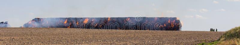 Impili il fieno in fuoco sul campo con i firemans fotografia stock