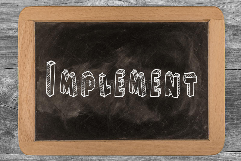 Implement - chalkboard. With 3D outlined text - on wood stock photo