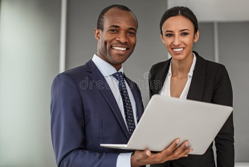 Positive businesswoman and businessman are standing in office with gadget stock photos