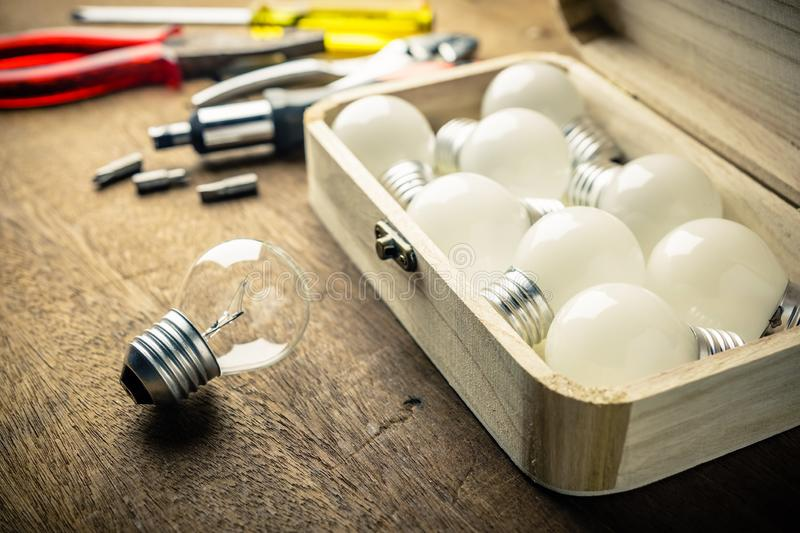 Implement Tools to Change Light Bulbs. Light bulbs and wood box with hardware tools on the desk, implement tools to change the light bulbs, DIY Do It Yourself royalty free stock images