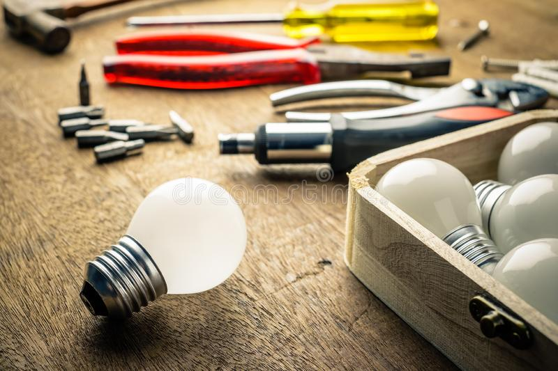 Implement Tools to Change Light Bulbs. Light bulbs and wood box with hardware tools on the desk, implement tools to change the light bulbs, DIY Do It Yourself stock image