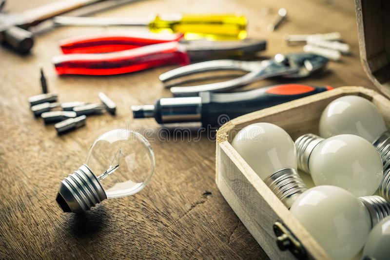 Implement Tools to Change Light Bulbs. Light bulbs and wood box with hardware tools on the desk, implement tools to change the light bulbs, DIY Do It Yourself stock images