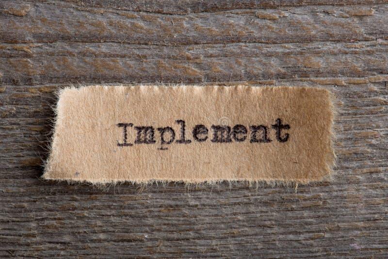 Implementar - palavra em um fim do pedaço de papel acima, conceito criativo da motivação do negócio imagens de stock