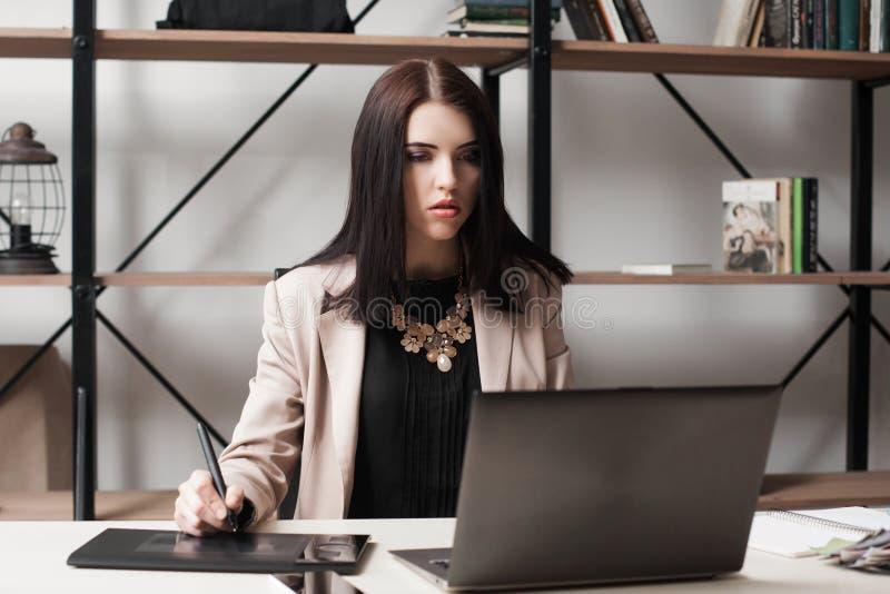 Imponerad affärskvinna som ser bärbar datorskärmen royaltyfria foton