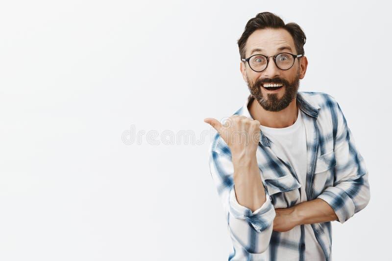 Imponerad lycklig och upphetsad snygg manlig forskare i exponeringsglas som tillbaka pekar eller lämnat med tummen och att stirra arkivfoto