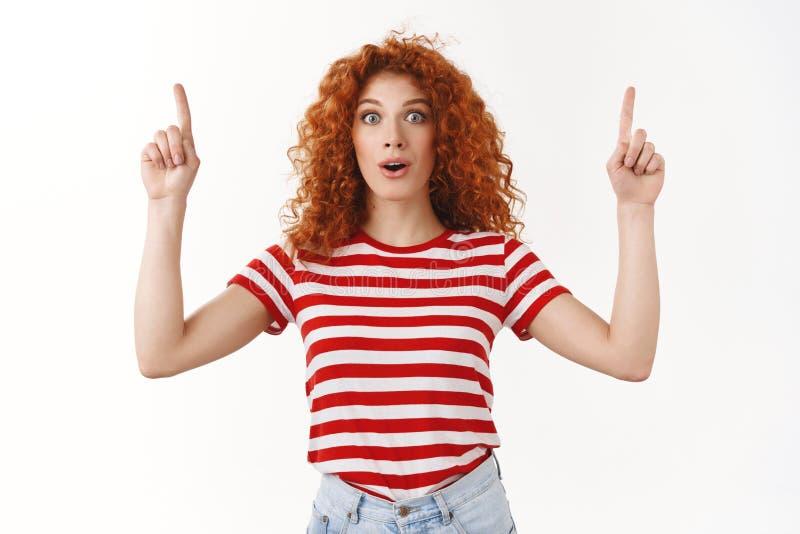 Imponerade hänförde breda ögon för ungt kvinnligt för rödhårig man som lockigt för kund hisnande enormt förslag för försäljning f royaltyfria foton