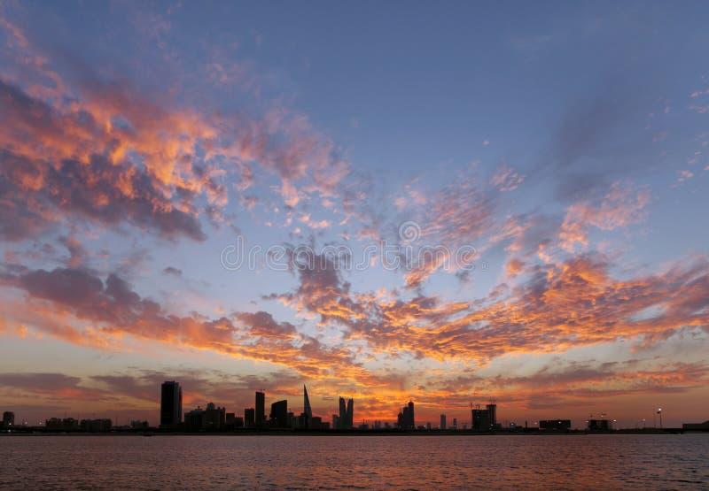 Imponerande föreställning som avviker moln & Bahrain horisont på solnedgång royaltyfri foto