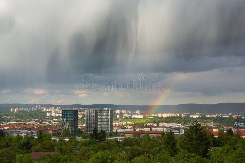 Imponerande föreställningmoln och regnbåge över stad royaltyfri fotografi