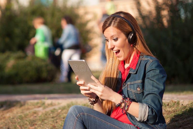 Imponerat och upphetsat lyssna för ung kvinna till musik på tablen royaltyfria bilder